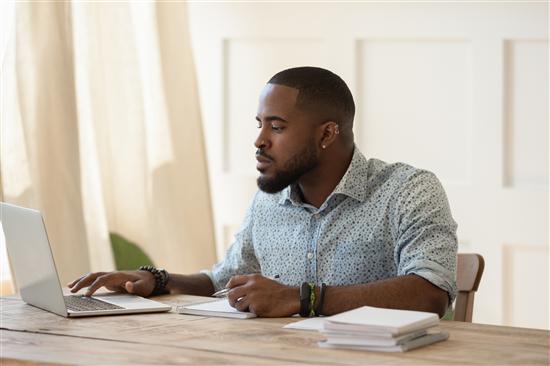 Image: man taking part in an online survey via a laptop